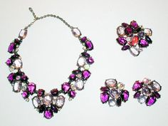 Schiaparelli Parure of Necklace, Pin and Earrings  USA, late 1950s  Oxidized metal findings, various shades of purple glass stones, some of which are aurora borealis stones, necklace 15 inches, pin2 1/2 inches, earrings 1 1/2 inches, signed: Schiaparelli.
