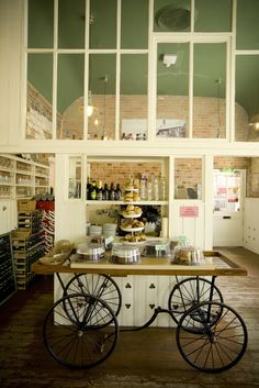 This could be used for pick n mix display that can be transported in and out of the lobby/cafe/bar before screenings. I like the use of the salvaged door and old buggy frame. {top 10 tea rooms South West}