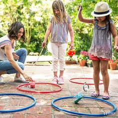 Bring the carnival home! This classic game is perfect for small-space areas like a patio. 1. First, fill two empty bottles with colored sand, available at most crafts stores. Next, tie a ring with string long enough to reach the ground. Attach the other end of the string to a wooden dowel. 2. Lay out Hula-Hoops and place a bottle on its side in the center of each one. 3. The game is over when someone can stand the bottle up./