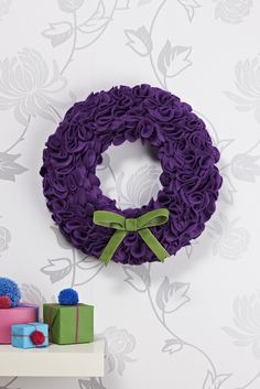 This sumptuous wreath is easy to make. Cut circles of felt and fold into a cone shape. Use pins to attach to a polystyrene ring and finish with a velvet bow. #ChristmasCraft #Wreath