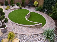 Creating a low maintenance garden doesn't mean you have to forego grassy areas. This unique design features a sloping circular garden area in a yin and yang style which is framed perfectly by our Deco Block Paving. #gardendesign #landscaping