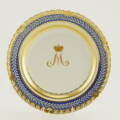"An Imperial Porcelain Factory dinner plate, from the Golden Service, St Petersburg, circa 1828. Of circular form, the cavetto painted with a gilt initial ""M"" below a crown for Empress Maria Feodorovna on white ground; the edge decorated with gilded rings and a gilt leaf blue band against the molded gilt rim."
