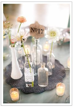 Pretty centerpieces using old vases and jars, found at a thrift store. Love the table number font and shape!