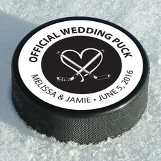 Hockey Puck Favor Label – features a heart behind two hockey sticks, with the phrase 'Official Wedding Puck' across the top and the couples name and wedding date at the bottom. It is a 2.5″ circle label that would be placed over top a hockey puck. #WeddingFavors