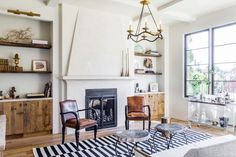 The stunning living room of Leigh Herzig featuring reclaimed wood cabinets, leather chairs and an antique chandelier