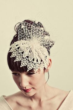 A silk covered skinny headband is hand sewn with intricate pale ivory venetian lace topped with a pouf of chenille dot ivory french netting