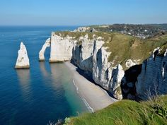 Cliffs of Etretat with the famous pointed Aiguille (Needle) and the natural arche the Porte d'Aval. Etretat is a commune in