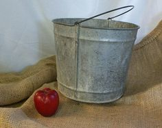 Rusty Bucket, Rustic Bucket, Rusted Bucket, Country Decor, Garden Decor. Galvanized zinc metal bucket with a swivel handle. This old bucket is rusty. Yard Art, Rustic Decor. It has a grey patina and pinhole on the bottom (see photo). No major dents (see photos) Beautiful rustic garden art or for your special use. Measurements 10 inches in diameter at the top. 9 inches tall. Handle swivels easily.  This is a rusty bucket. Please consider the vintage condition as rusty and deteriorating. It is…