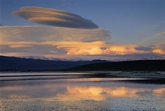 Lenticular Clouds, technically known as altocumulus standing lenticularis, are stationary lens-shaped clouds that form at high altitudes, normally aligned at right-angles to the wind direction.