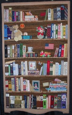 Margaret Kessler's quilt, BBK - Bookcase Before Kindles  Fabrics include cottons and pieces from husband's ties.  Labels from clothes, hats, shoes, sleeping bag, quilt friends, selvage edges of fabric, and thrift center items were added for book titles.