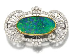 OPAL AND DIAMOND BROOCH, CIRCA 1910. Set with a polished opal within an openwork frame millegrain-set with circular- and single- cut diamonds.