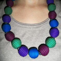 Una collana che unisce viola, vino, smeraldo, azzurro di cielo in un gioielli etnici. È di forma molto particolare e allinea il reticolo.  È lungo