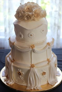 Very elegant all buttercream wedding cake with drapes, pearls and handmade gold sugar roses.  Inspired by a cake in the book Cake Walk.
