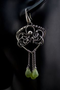 Long, feminine, romantic and eye-catching dangle earings. Made entirely by hand from fine and sterling silver wire with silversmiths and wire wrapping technique. Green drops of natural peridote dance when move them. Patinated and polished. ____________________  Total lenght is 8,5 cm ( 3.35 inch) Width 3,5 cm (1.38 in) Weight of each piece is 10,37 gr. ____________________  Do not wet. ____________________  Certain metal after a small time slightly darken. You can clean silver jewelry with…