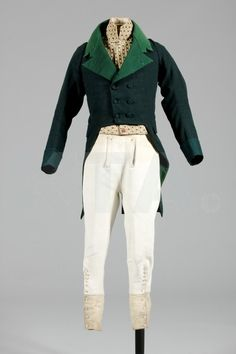 French, c.1810-20, with paler green facecloth linings, lapels with sharp M notches, cut high and square at the waist, horizontally quilted chest panels, narrow kite-shaped back and deep armholes, pocket flaps concealed within the tails; the soft white leather breeches, c.1800-10, with narrow small-fall and bone buttons, the lower legs with extenders for wearing inside boots, mother of pearl buttons; the waistcoat of striped 1780s velvet with high stand collar.
