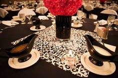 Centerpieces, tissue paper pomanders sit on a black cylinder on black & white fabric squares.
