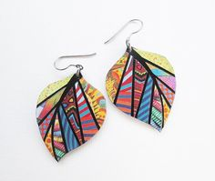 These earrings are one-of-a-kind, hand-pieced, paper mosaic works of original art. The reverse side shows a simplified, complimentary image - in the photo with the coin. The earrings are made from paper glued to painted vinyl. I cut the vinyl shapes from reclaimed flooring samples, painted them with acrylic paint, then glued on paper found in magazines and discarded books. The earrings are protected with a first coat of Mod Podge, and a second coat of UV Resistant Acrylic Spray, which…