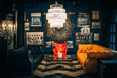 Dark blue painted walls, murano chandelier; black leather Chestershire; Goldenn leather Chestershire, orange leather chair; chevron rug, Los Angeles Athletic Club