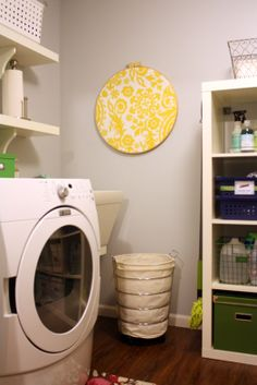 Functional wall art.... bright yellow fabric in a jumbo embroidery hoop in the laundry room for pinning extra buttons, etc.