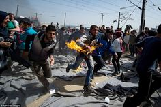 A man runs after he tried to set himself on fire during a protest at a makeshift camp at the Greek-Macedonian border near the village of Idomeni in the wake of the EU's new deal with Turkey to send back asylum seekers with no legitimate claims