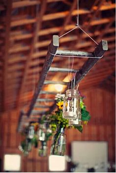 Mason jars for candles and flowers hanging from a ladder.