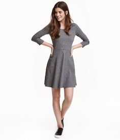 Black. Short jersey dress with 3/4-length sleeves and a slightly wider neckline. Seam at waist and circle skirt. Unlined.