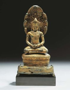 a khmer, angkor vat style, gilt-bronze figure of buddhamuchalinda 12th century Seated in vajrasana on the coils of the snake which seven heads serve as canopy, placed on a rectangular base, both hands in dhyanamudra and holding bowl, wearing sampot, his face serene expression 17 cm high, mounted