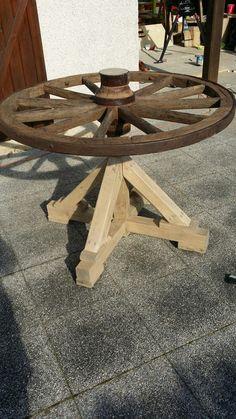 Table en bois fabriquée à partir d'une roue de charette. Le pied est fait en chevron de palette.