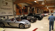Leno walks through the airplane hanger where he stores his collection. To the left is his Porsche Carrera GT.