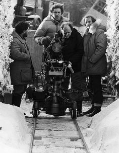 Grip Dennis Lewis, Assistant Director Brian Cook, Camera Operator Kelvin Pike, and Camera Assistant Douglas Milsome set up a shot for The Shining in the exterior hedge maze set on the backlot of Elstree Studios.