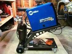 Welding Cart by RegalX -- Homemade cart for a Miller MIG welder fabricated from steel and incorporating large rear casters for increased stability. Tank retention strap was fashioned from leather and secured by a riveted brass clasp. http://www.homemadetools.net/homemade-welding-cart-12