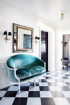 Blue velvet love seat in entryway with tiled floor,  and antique mirror
