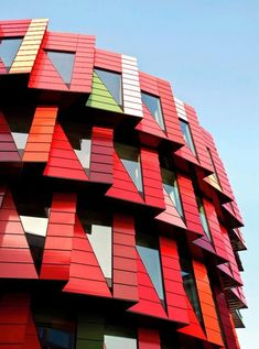 """Chalmers University of Technolgy """"Kuggen"""" in Gothenburg, Sweden designed by architect Wingårdh Arkitektkontor AB. The skin is glazed terracotta made of 6 different shades of red & a one green. """"Kuggen"""" is circular & every floor level adds 2 bays making the building grow in size for every added floor. A movable sunscreen tracks the sun & adds to the shade to the 2 top floors. The windows are triangular allowing daylight to follow the ceiling deep into the building (WorldBuildingsDirectory)"""