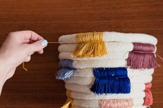 How To Make a DIY Colorful Fringe Coiled Plant Holder | With some simple supplies, a spare hour or two, and an itch for creating cool color combos, you can easily craft a playful new look for all of your plants. The coiled cotton piping offers the ultimate neutral base for all of your favorite embroidery floss hues, and it makes this DIY perfect for pairing with all things textured, natural and bright