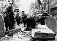 Officers inspecting the damage to the Berlin Wall, East Germany, and making preparations for its repair, after an East German rammed the Wall with an army car and successfully escaped. (Photo by Keystone/Getty Images). 1963