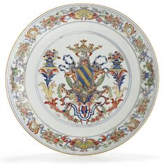 A PORTUGESE MARKET ARMORIAL DISH  CIRCA 1720  The center with the large coat-of-arms of Ataide in Chinese Imari colors and gilt supported by a pair of herms bearing smoking urns on their heads, rising from scrolling brackets and clasping drapery which hangs down from the canopy that is over all, on the rim the bull's head crest twice amid scrolling, flowering vine  13 1/8 in. (33.3 cm.) diameter