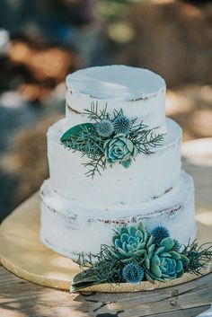 simple white iced wedding cake with blue + green florals + succulents