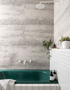concrete walls + white stacked subway tile with black grout + green tub + white fixtures