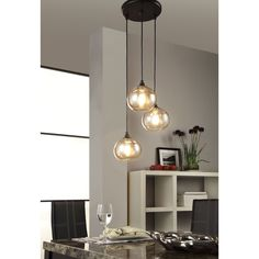 This sophisticated Uptown cluster pendant features three lights, grouped together and artfully suspended at various heights. Each fixture houses a stylish Edison-style bulb in a warm, amber colored glass globe for a metro-mod motif.