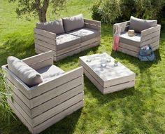 une table basse en palette et des chaises hautes avec des coussins gris moelleux