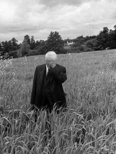 Robert Frost standing in a field in Oxford, England in 1957 with his hand over his face. Photo by Howard Sochurek