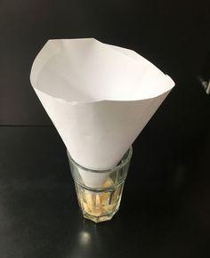 Bananflue fælde lavet af en papirtragt og et glas med frugtrester og vand.