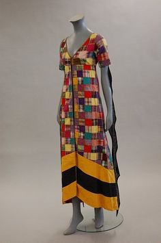 A Thea Porter patchworked tunic, early 1970s, couture labelled, composed of a patchwork of madras cottons, yellow and black striped hem, black gothic streamers to the sleeves