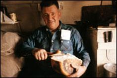 A sheepherder cuts a loaf of bread.  As they moved across the mountains of Idaho, Montana, Nevada and California, immigrant Basque sheepherders cooked in Dutch ovens covered by dirt in pits they dug in the ground. Below are recipes for sheepherder bread, lamb stew and Basque boardinghouse flan.