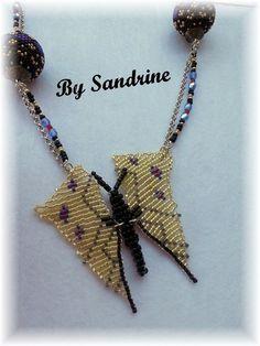 Collier papillon jaune, modèle unique fait main by Sandrine.  Les ailes du papillon sont réalisées en tissage à plat de perles japonaises jaunes, bleues, rouges, grises et noires. Le corps du papillon est un tissage en relief de rocailles noires. Le collier comporte 2 perles rondes en bois recouvertes d'un tissage peyote de perles japonaises noires, bleues, rouges et dorées