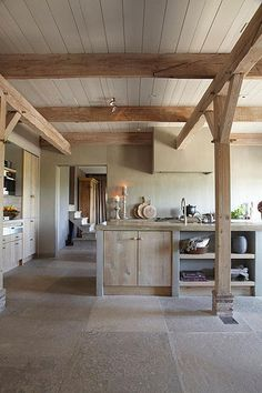 Kitchen with furniture made of wood and concrete and a floor made of big stone tiles via The Style Files