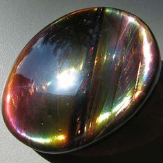 "Precious Fire Obsidian     48 x 38 mm. 134 cts. Precious Fire obsidian is a material which only occurs on Glass Buttes in central Oregon. It has extremely thin layers of minerals which break up light into spectacular, shifting colors. This material is not the same as ""rainbow"" obsidian, or other sheen obsidians. Recently, some doublet and triple stones have hit the market which incorporate a layer of Paua abalone shell to imitate the effect."