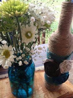I have lots of these wine bottles for sale! Diy centerpieces,  blue mason jars, twine wrapped wine bottles, fabric flowers,  teal & brown wedding, diy wedding decor