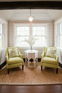 Small sitting area off the kitchen. We used lime green upholstered armchairs to make this sweet area off of the kitchen into a cozy nook for 2. We love moments like this in living spaces to bring interest points throughout a space and draw the eye. A braided sisal rug is the perfect ground for this bold statement and we love the feel of the Moroccan inspires occasional table. #nantucketinteriordesign #staging #limegreen #readingnook #sittingarea