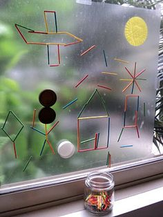 An art activity using contact paper taped to a window, with colored matchsticks and water bottle lids.